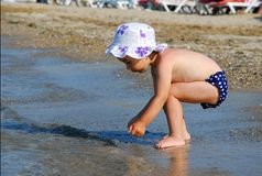 Little girl looking for shells on the beach Royalty Free Stock Images