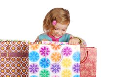 Little girl looking in shopping bags Royalty Free Stock Images
