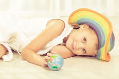 Little girl looking at a small globe Royalty Free Stock Photo
