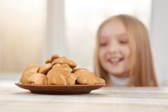 Little girl is looking on sweet cookies and looks hungry. Hungry girl with blonde straight hair and big brown eyes is looking on delicious flower-shaped cookies Royalty Free Stock Photography