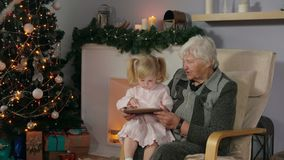 Girl with her grandmother looking at the tablet photos stock footage