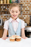 Little girl looking at tasty cakes on plate Stock Photography
