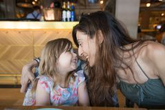 Little girl looking to mother laughing in restaurant Stock Photography
