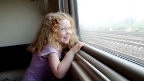 Little girl looking in the train window and laughing stock video footage