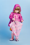 Little girl looking at umbrella Stock Image