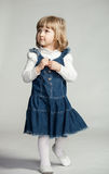 Little girl looking up. In blue dress on dark background Royalty Free Stock Photography