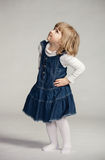 Little girl looking up. In blue dress on dark background Royalty Free Stock Image