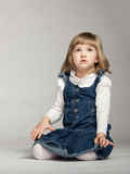 Little girl looking up and sitting on the floor Stock Photography