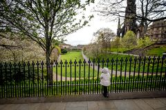 Little girl looking at view from Prince Street Gardens, with People walking along the gardens during a rainy day in. People walking along Prince Street Gardens stock photos