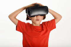 Little girl looking in VR glasses and gesturing with his hands. Stock Images
