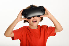Little girl looking in VR glasses and gesturing with his hands. Stock Photo
