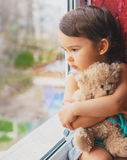 Little girl looking through window with teddy bear Royalty Free Stock Photos