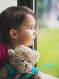 Little girl looking through window with teddy bear Stock Image