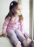 Little girl looking through the window Stock Image