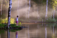 Little girl looks at beautiful lake with steam above water Royalty Free Stock Images