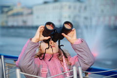 Little girl looks through binoculars at sunset Royalty Free Stock Photos