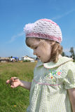 Little girl looks at blade of grass village Royalty Free Stock Photos