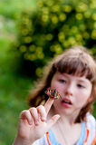 Little girl looks at a butterfly. Aglais urticae L. Stock Image