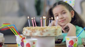 A little girl looks at a cake with candles stock footage
