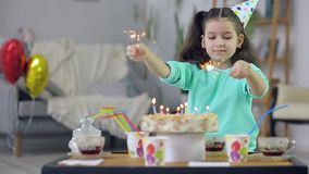 The little girl looks at the cake and lights the sparklers stock video