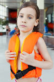 Little girl looks at camera after swimming. Little sorrowful girl wearing orange life-jacket looks at camera after swimming in pool Stock Photo