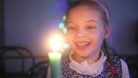 Little girl looks candle and dreams. New Year decorations Christmas tree. Little girl looks candle and dreams. New Year decorations Christmas tree stock video