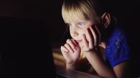 Little girl looks cartoon on the laptop. Luminous laptop screen illuminates the child`s face. Little girl looks cartoon on the laptop stock footage