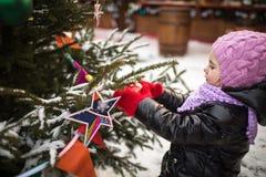 Little girl looks at christmas decor Stock Photo