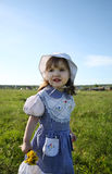 Little girl looks into distance on green field Stock Photography