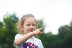 A little girl looks into the distance, says something and points a finger royalty free stock photo