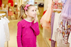 Little girl looks upon dresses hanging at stand Royalty Free Stock Photo
