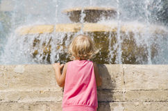 Little girl looks at the fountain. Stock Photography