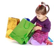 Little girl looks at the gifts in a big green bag Royalty Free Stock Photo