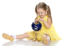 A little girl looks at the Globe. The concept of science, geography, school, happy childhood. Isolated on white background Stock Photography