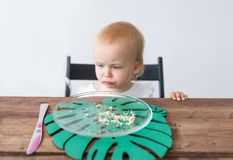 The little girl looks with grief at empty and dirty dessert dish on wooden table.  Royalty Free Stock Photography
