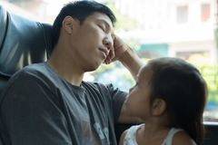 Little girl looks at her tired dad while he`s sleeping on the bus royalty free stock photography