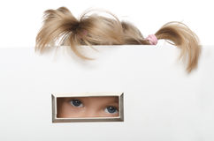 Little girl looks inquisitively out of box Royalty Free Stock Photos
