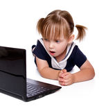 The little girl looks in a laptop. The surprised little girl looks in a laptop Stock Photography