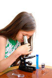 Little girl looks through microscope Royalty Free Stock Images