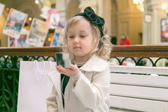 Little girl looks in the mirror. Sitting on a bench in the mall Royalty Free Stock Images