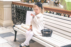 Little girl looks in the mirror. Sitting on a bench in the mall Royalty Free Stock Photos