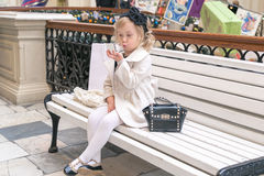 Little girl looks in the mirror. Sitting on a bench in the mall Stock Image