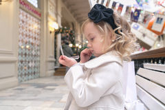 Little girl looks in the mirror. Sitting on a bench in the mall Stock Photo