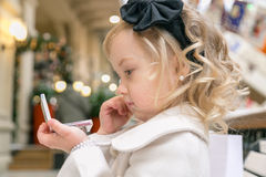 Little girl looks in the mirror. Sitting on a bench in the mall Royalty Free Stock Image