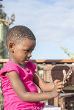 Little Girl Looks at Mobile Phone Screen. Royalty Free Stock Photography