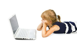 Little girl looks in the monitor. Thinking girl on the floor in front of a silver laptop Stock Photography