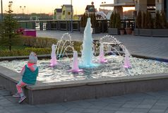 Little girl looks at the fountain at sunset on the Embankment of the city Royalty Free Stock Images