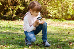 Little girl looks at nature through a magnifying glass Stock Image