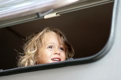the little girl looks out of the camper window royalty free stock photography