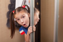 Little girl looks out of the closet. Hide and seek theme stock photos